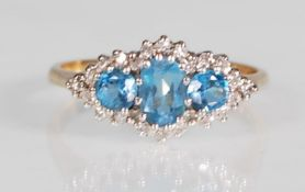 A hallmarked 9ct yellow gold ring set with a central oval faceted cut blue topaz flanked by two