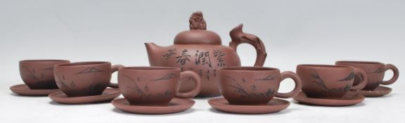 A Chinese Yixing clay teapot having carved decorat