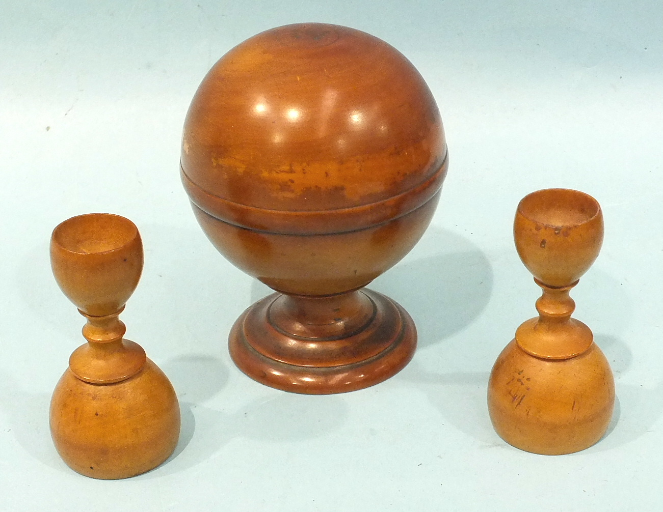 Lot 252 - A 20th century polished boxwood pill roller of spherical form raised on a plinth, stamped S Maw &