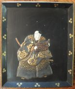 Lot 250 - An early 20th century lacquered wood shallow tray decorated in relief with a Samurai reading from