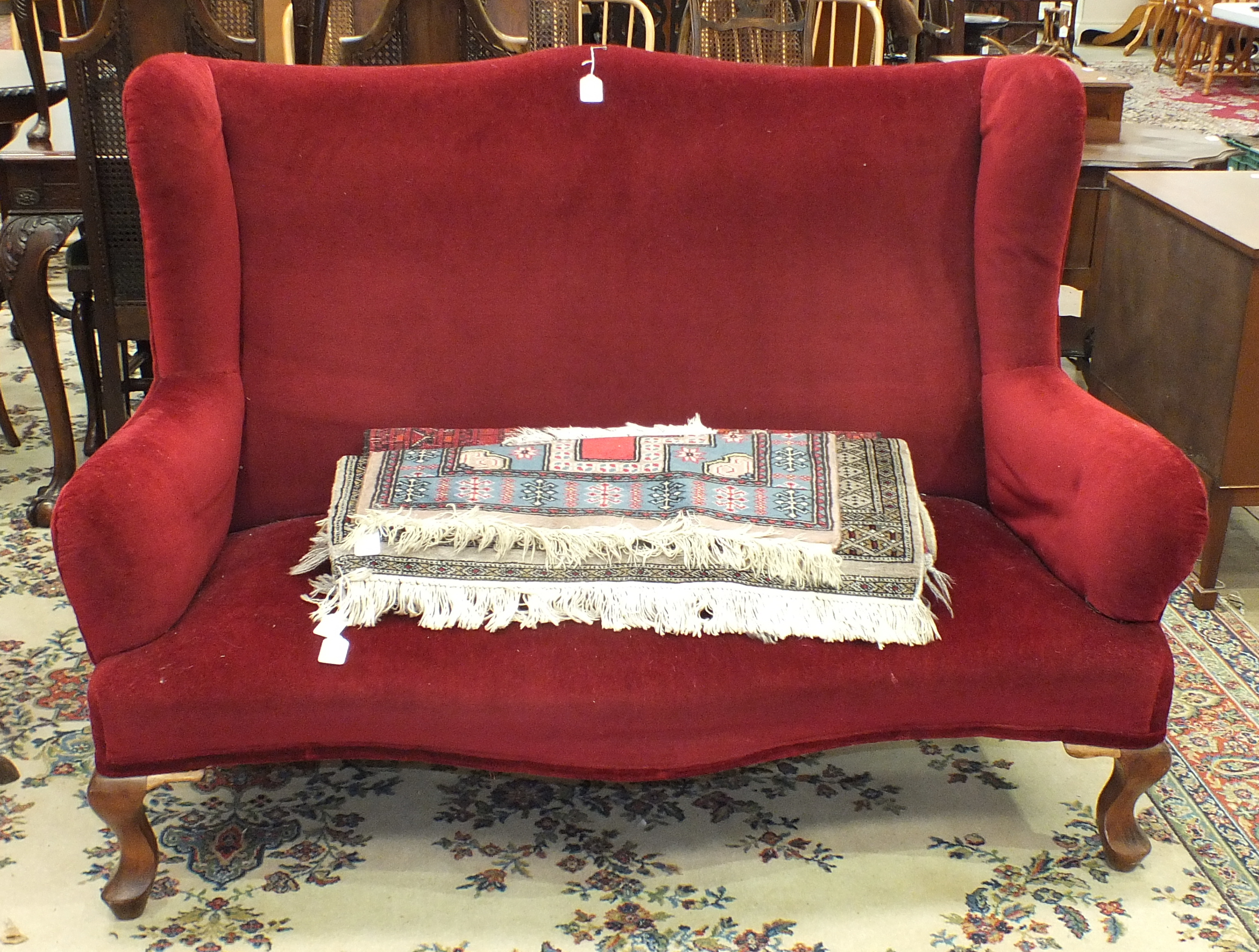 Lot 31 - An early/mid-20th century upholstered two-seater wing-back settee on cabriole legs, 140cm wide.