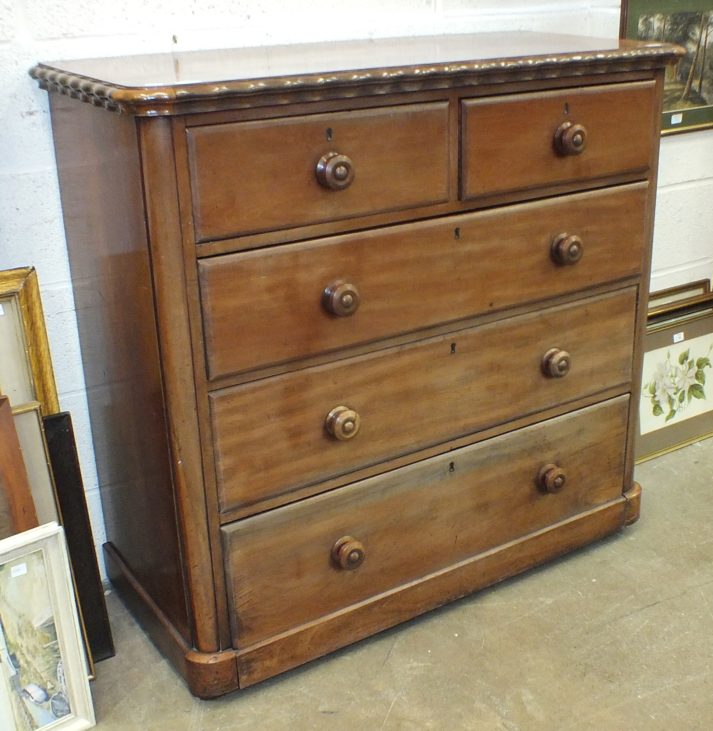 Lot 4 - A mahogany finish straight-front chest, the rectangular top with wavy edge above two small and three