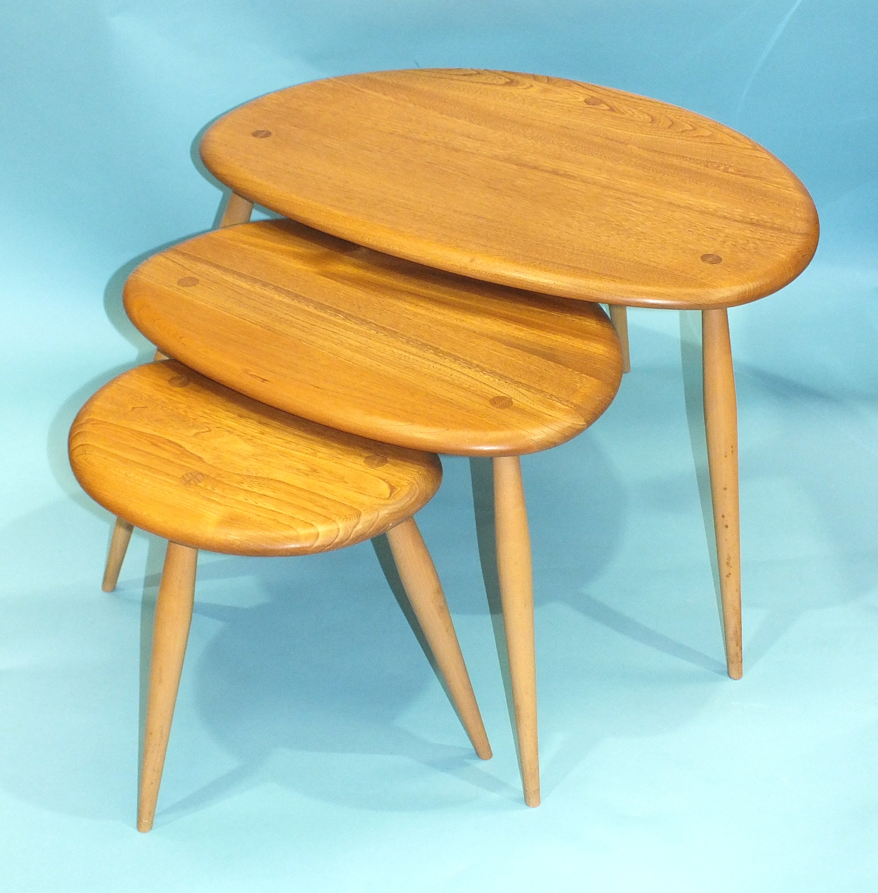 Lot 48 - An Ercol nest of three light elm and beech 'Pebble' tables, largest 64cm wide, 41cm high.