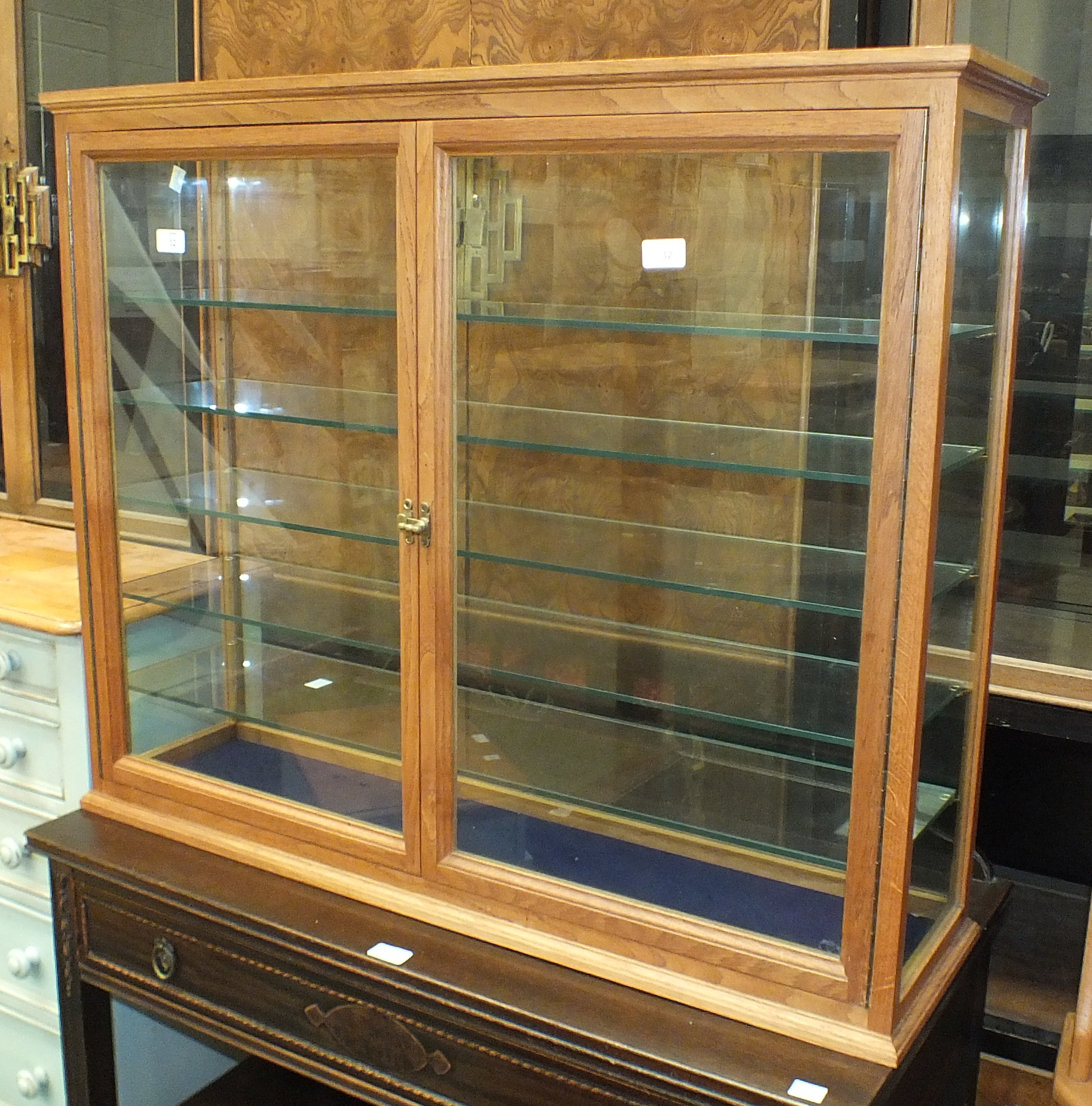 Lot 32 - A modern display cabinet with grained wood frame, glass back and sides and a pair of glazed doors,