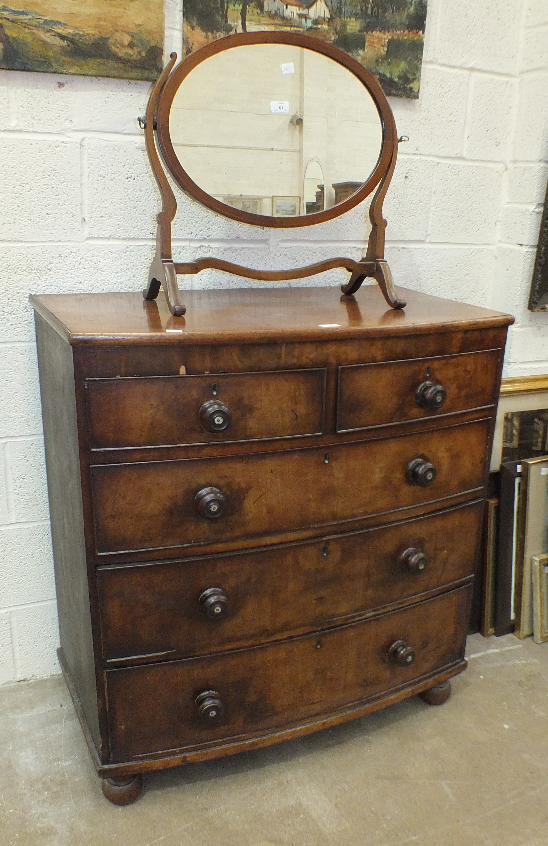 Lot 61 - A 19th century mahogany bow-fronted chest of two short and three long cockbeaded drawers, on