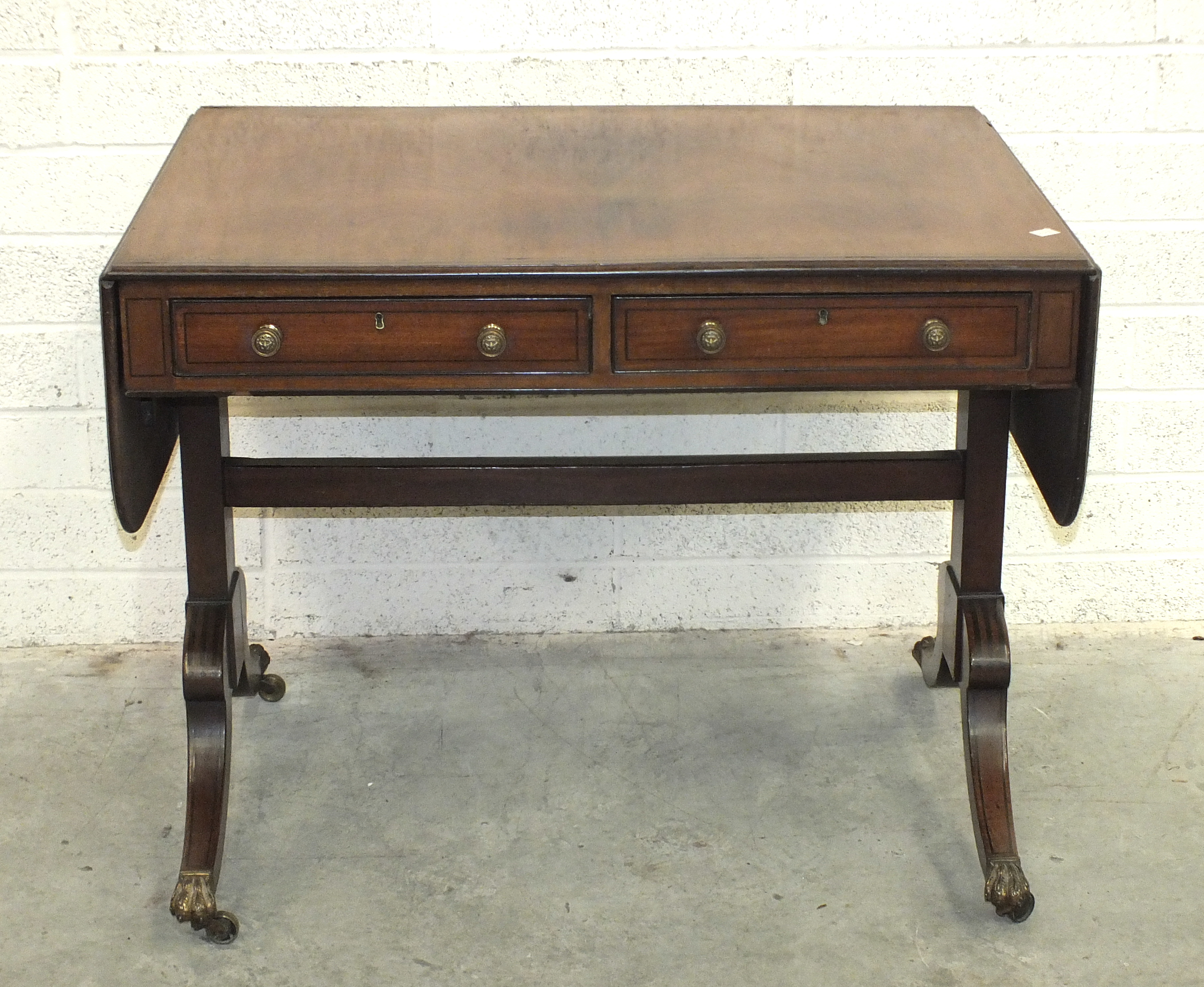 Lot 88 - A Regency ebony-strung sofa table, the rectangular top with two drop leaves, above two cockbeaded