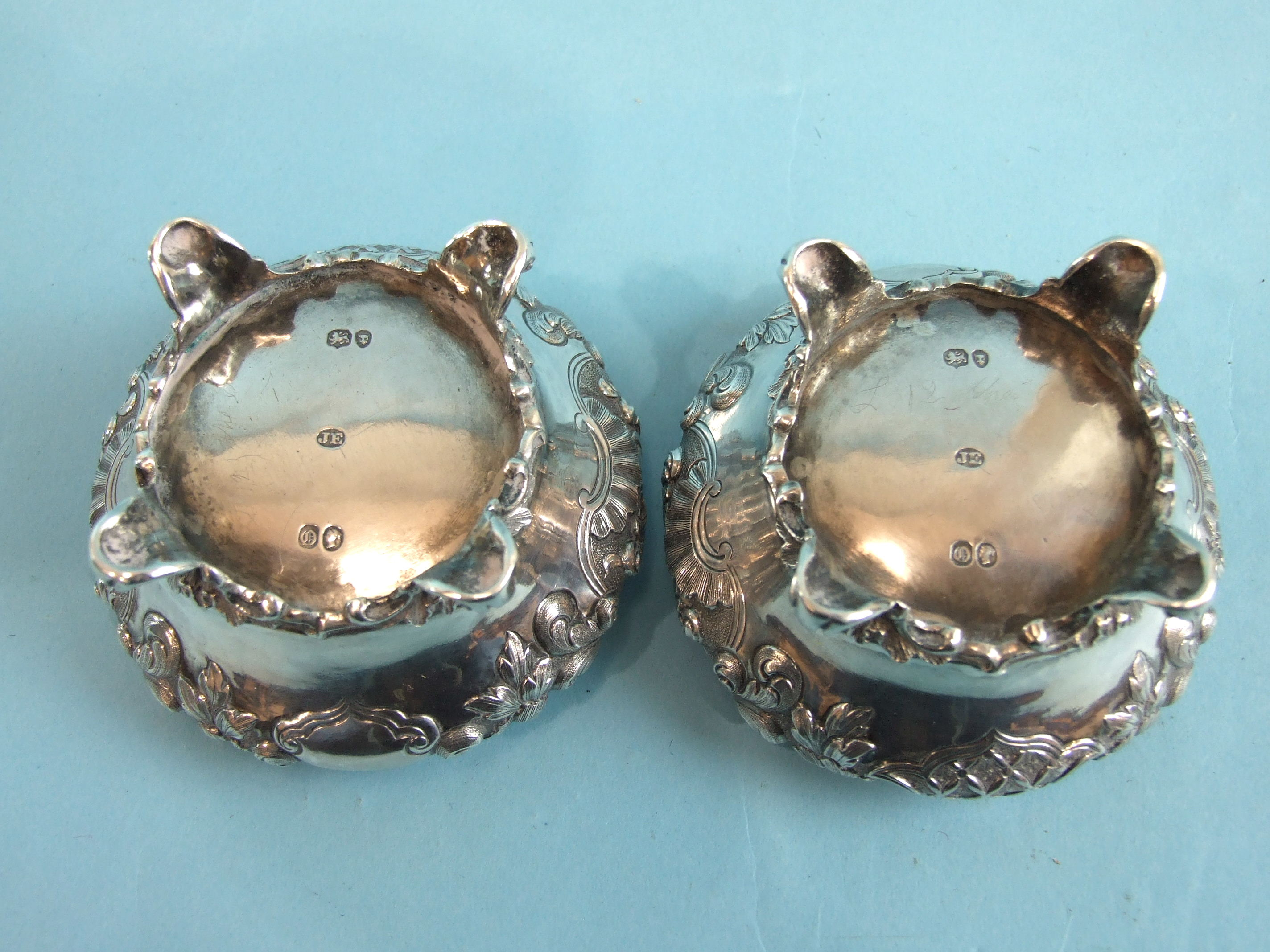 Lot 330 - A pair of Victorian salts of compressed circular form embossed with flowers and foliage, on four