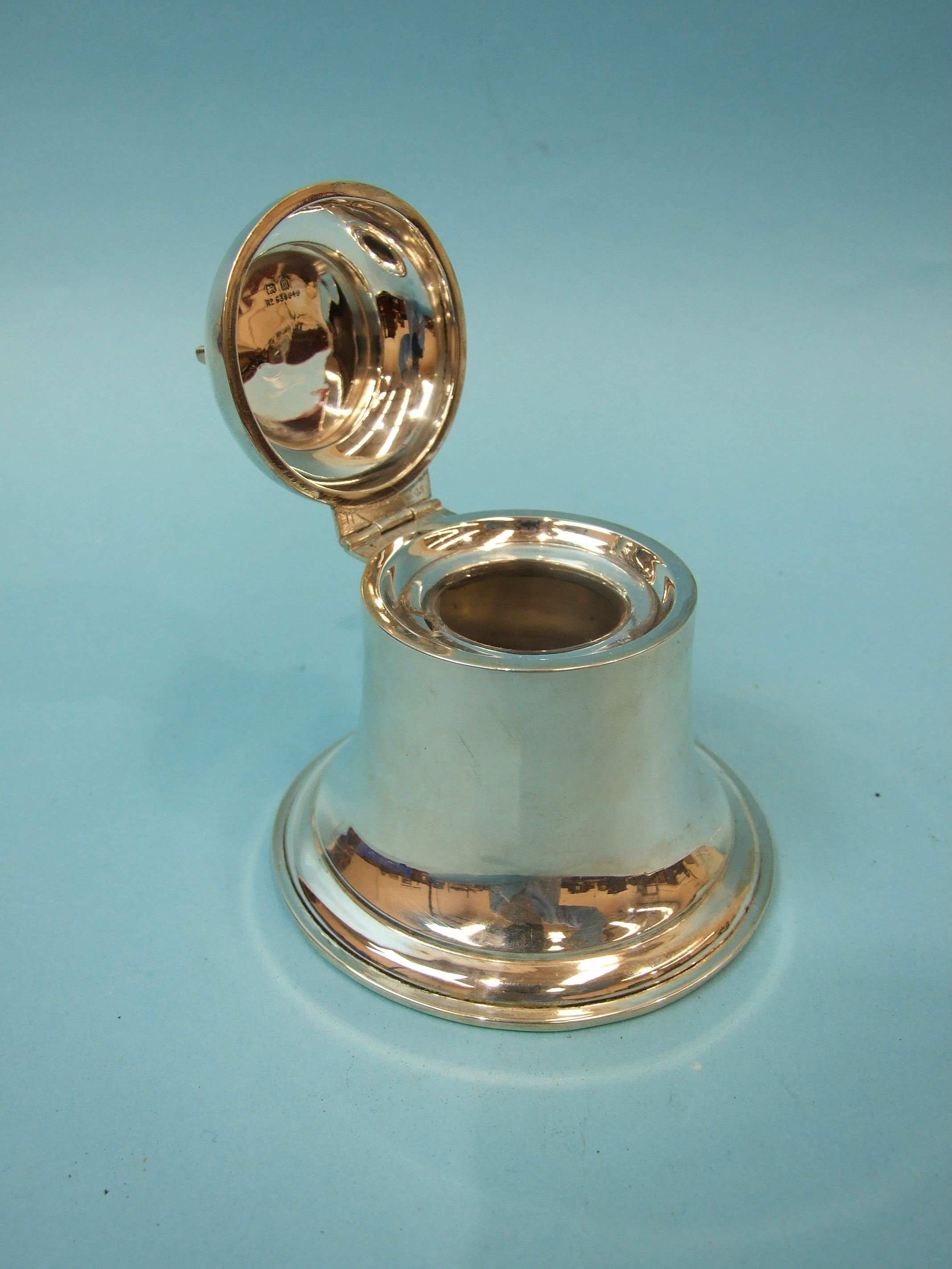 Lot 335 - An early-20th century silver inkwell in the form of a bell, (glass liner chipped, weighted base),