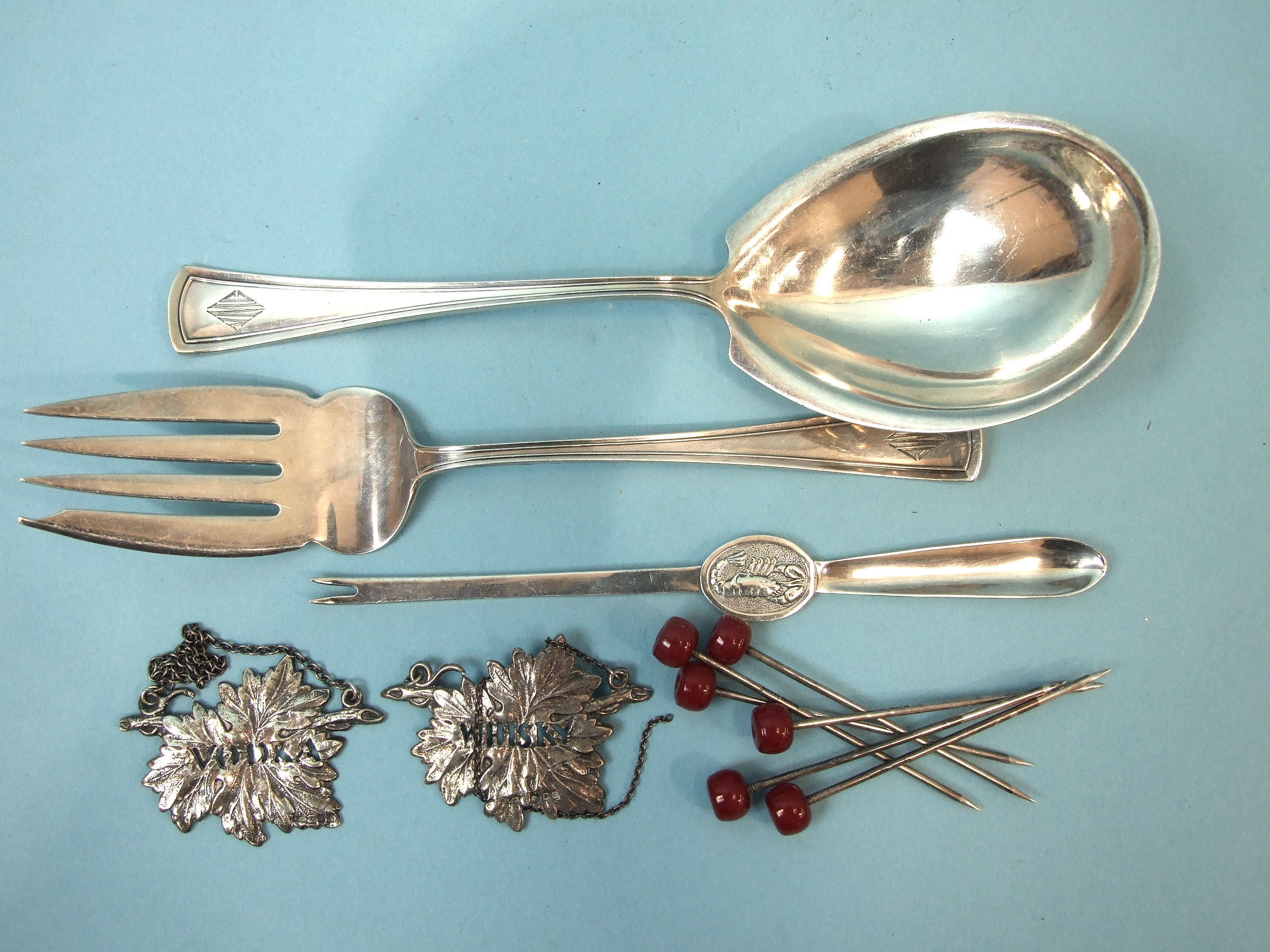 Lot 342 - A pair of sterling silver salad servers, a silver lobster pick, a pair of pierced silver spirit