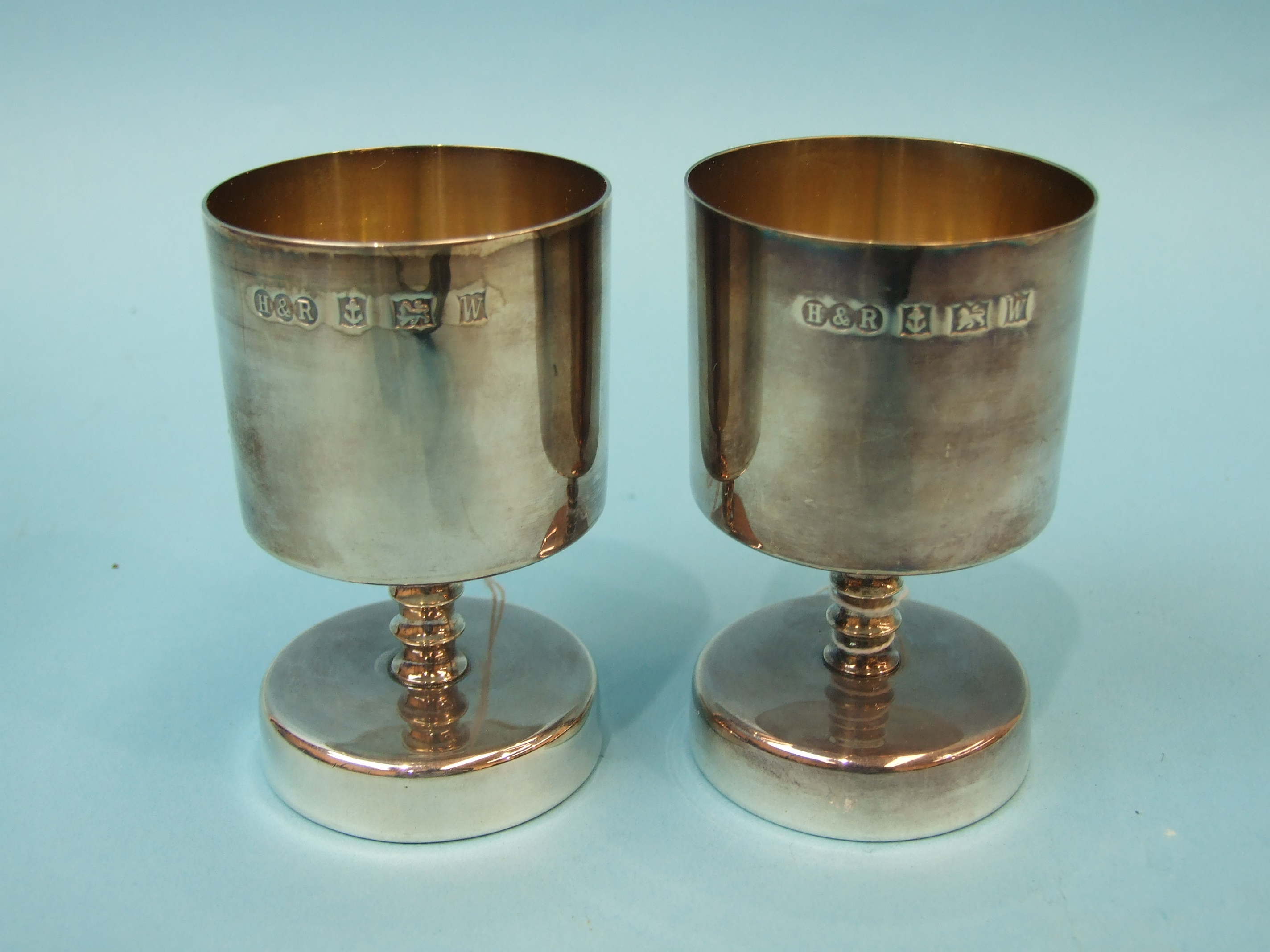 Lot 339 - A pair of modern silver goblets of squat form, each with slightly-tapered bowl and knopped stem