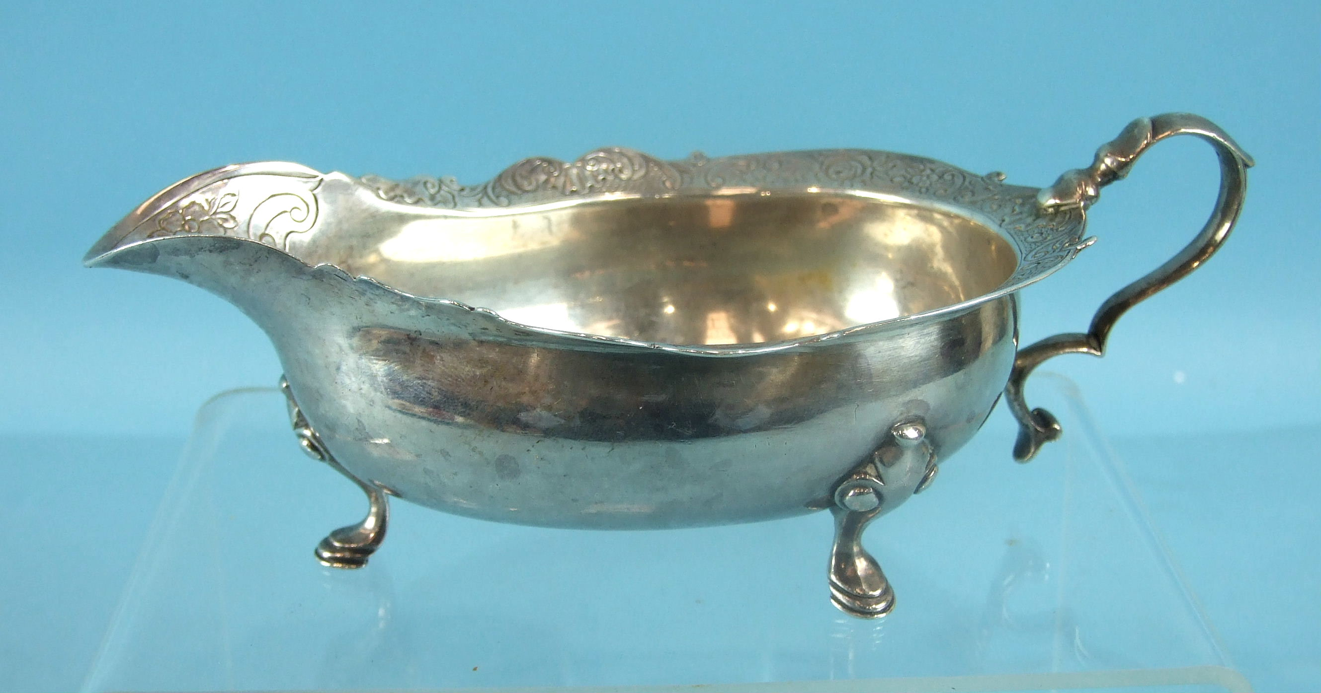 Lot 329 - A George II Scottish cream or sauce boat on three hoof feet, with a shaped and chased rim and scroll