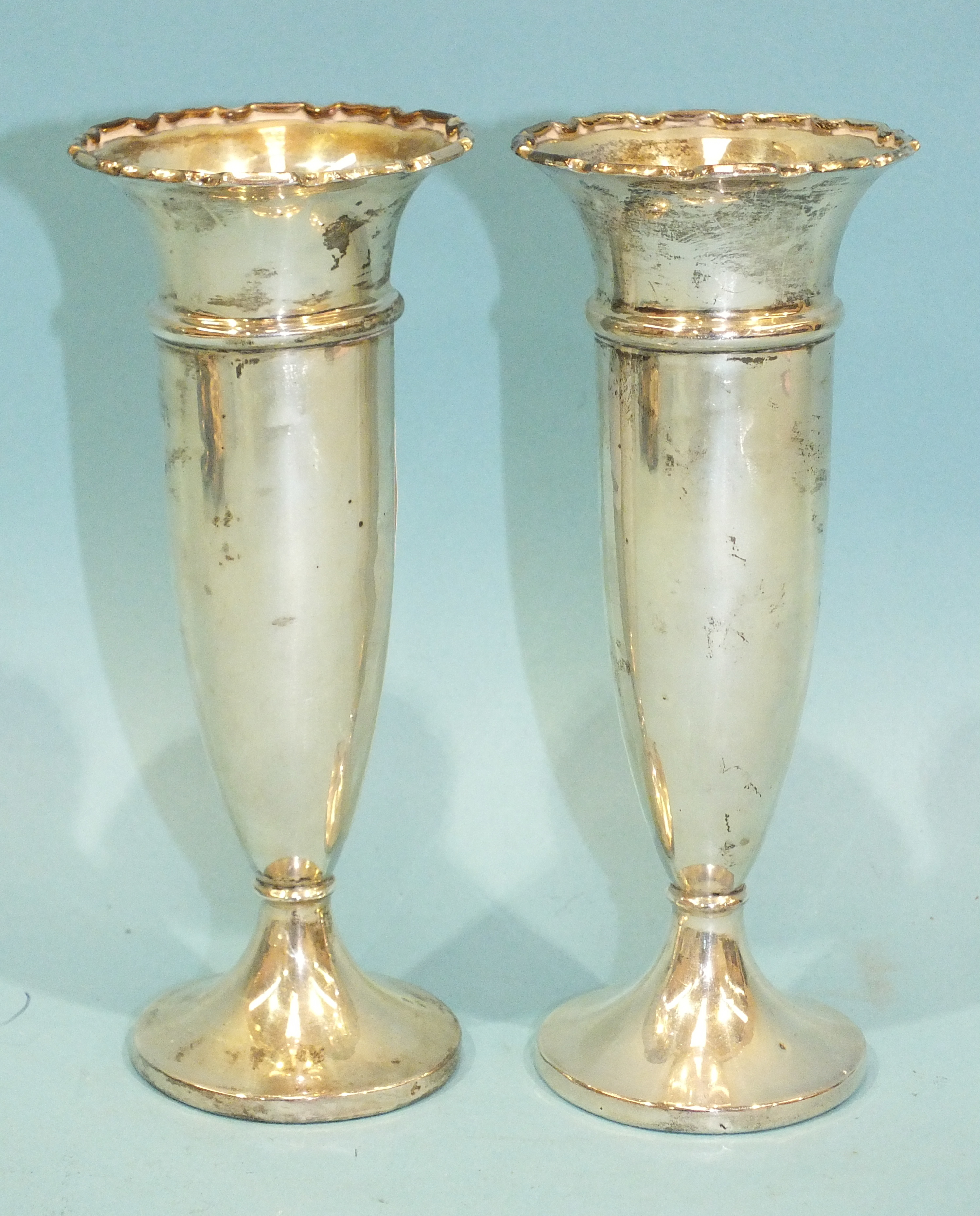 Lot 196 - A pair of silver spill vases with loaded bases, Birmingham 1914, 13.5cm high, (2).