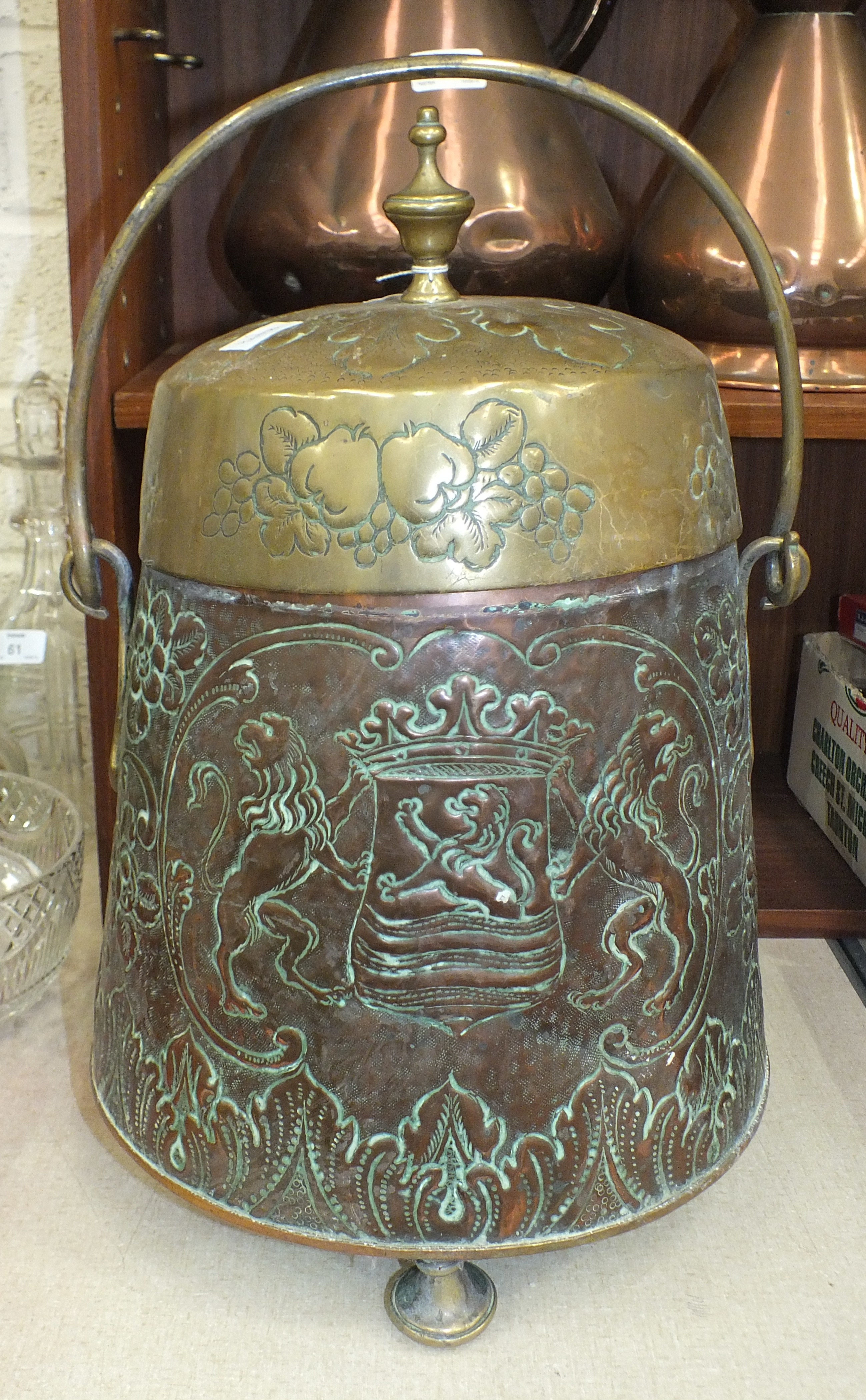 Lot 62 - A copper coal box of circular tapering form, embossed with the Dutch coat of arms and a rural