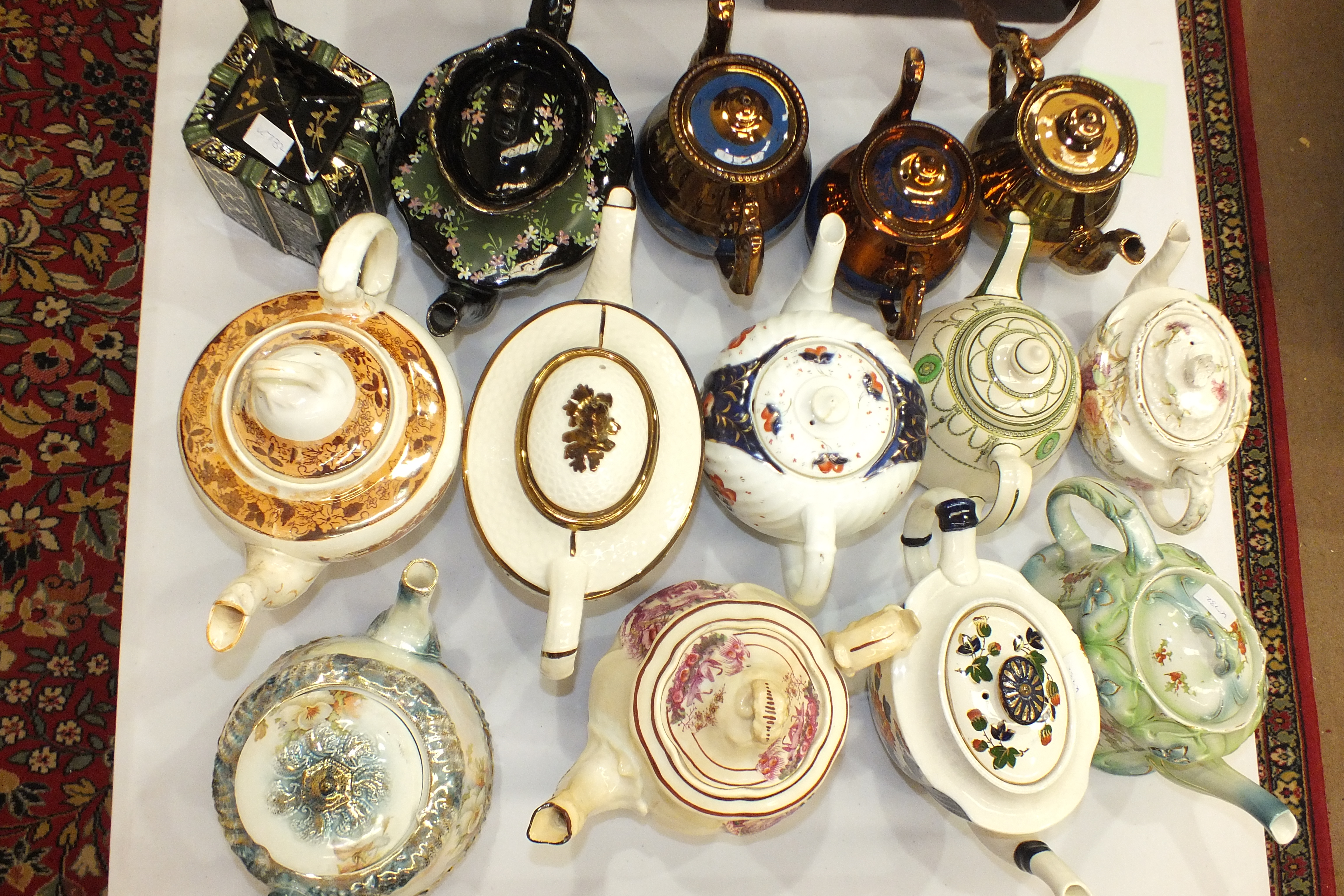 Lot 111 - A collection of fourteen 19th century lustre and other teapots.