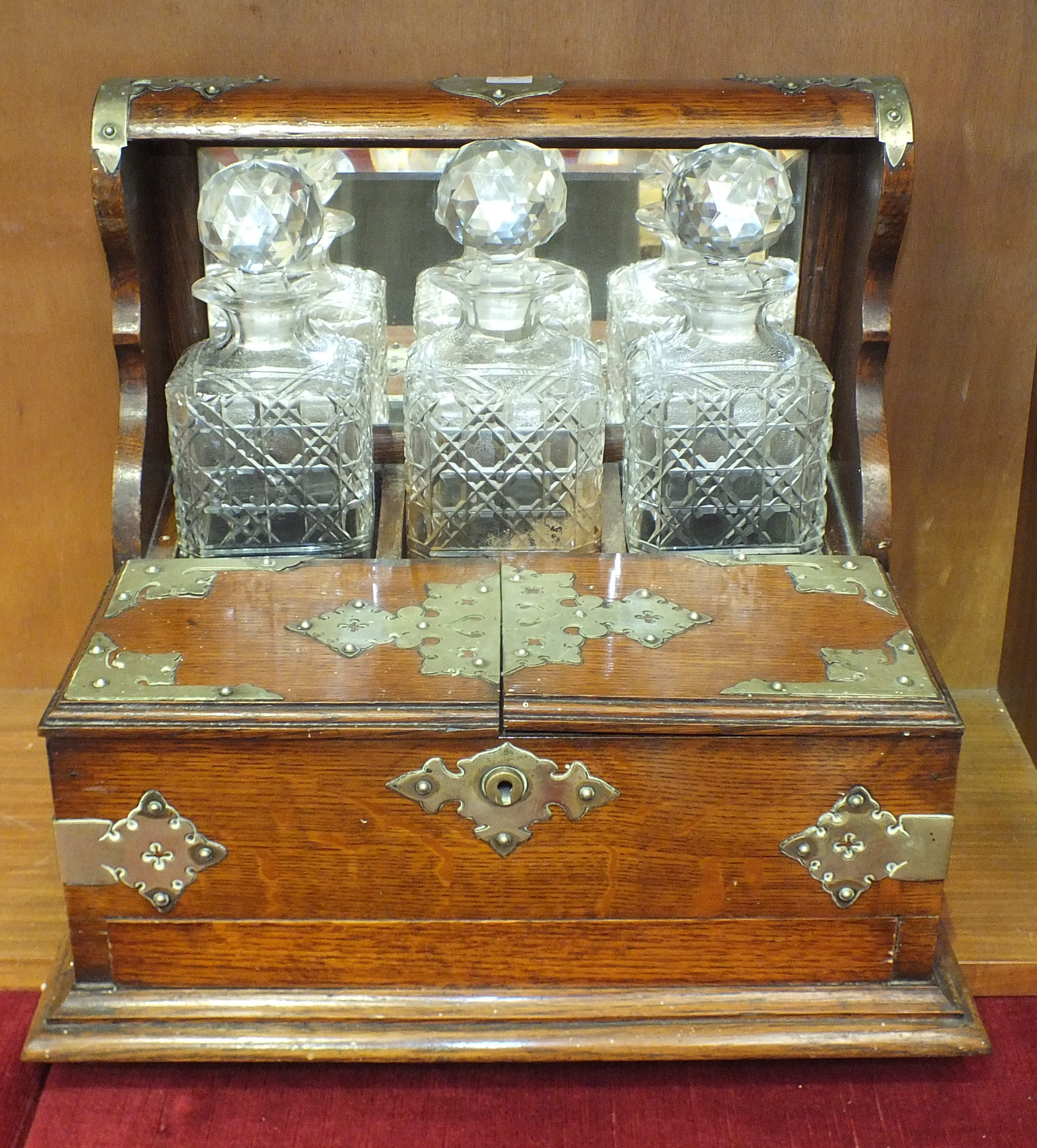 Lot 70 - An Edwardian oak Tantalus with plated mounts and compartments for glasses, 33cm high, 38cm wide.