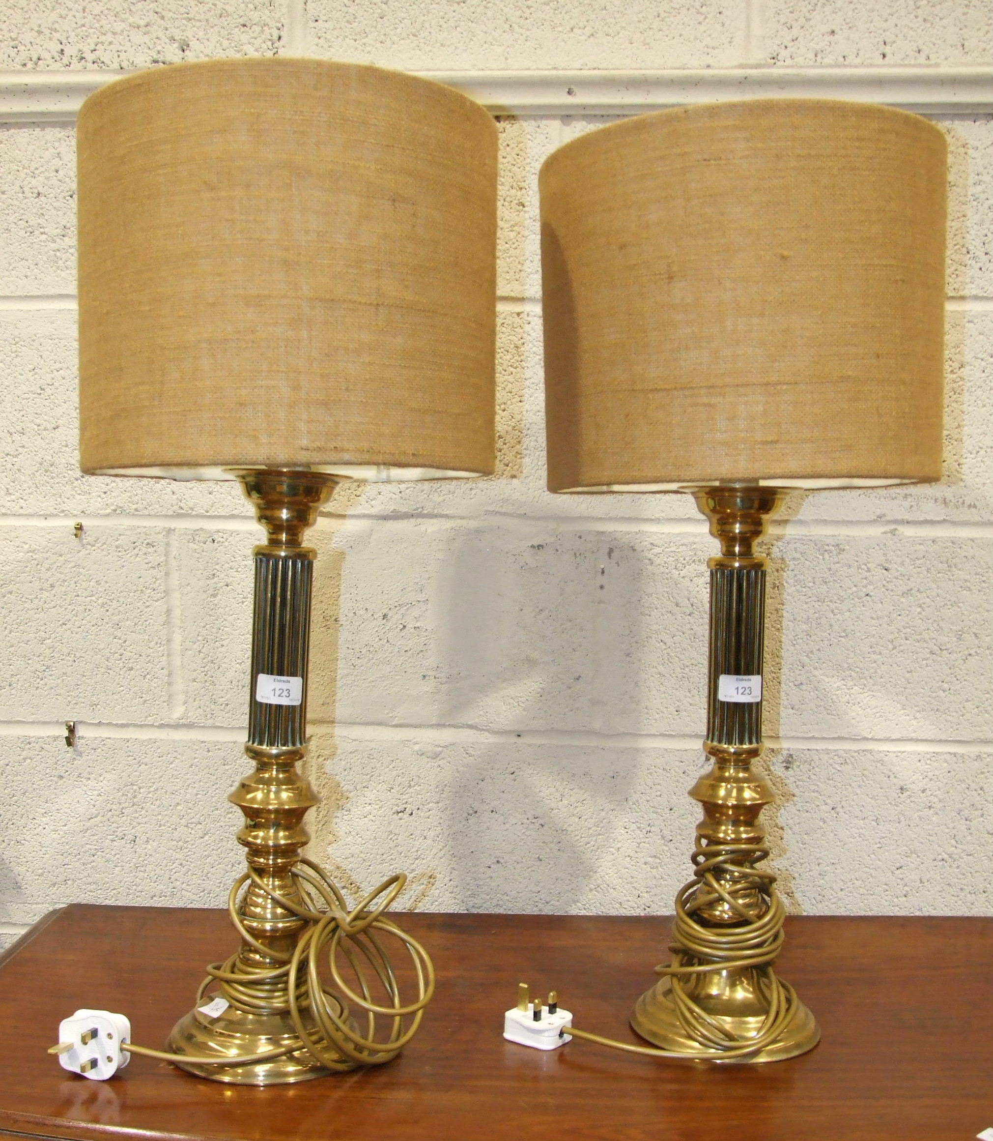 Lot 123 - A pair of brass table lamps with reeded and turned columns, on circular bases, 51cm high, (2).