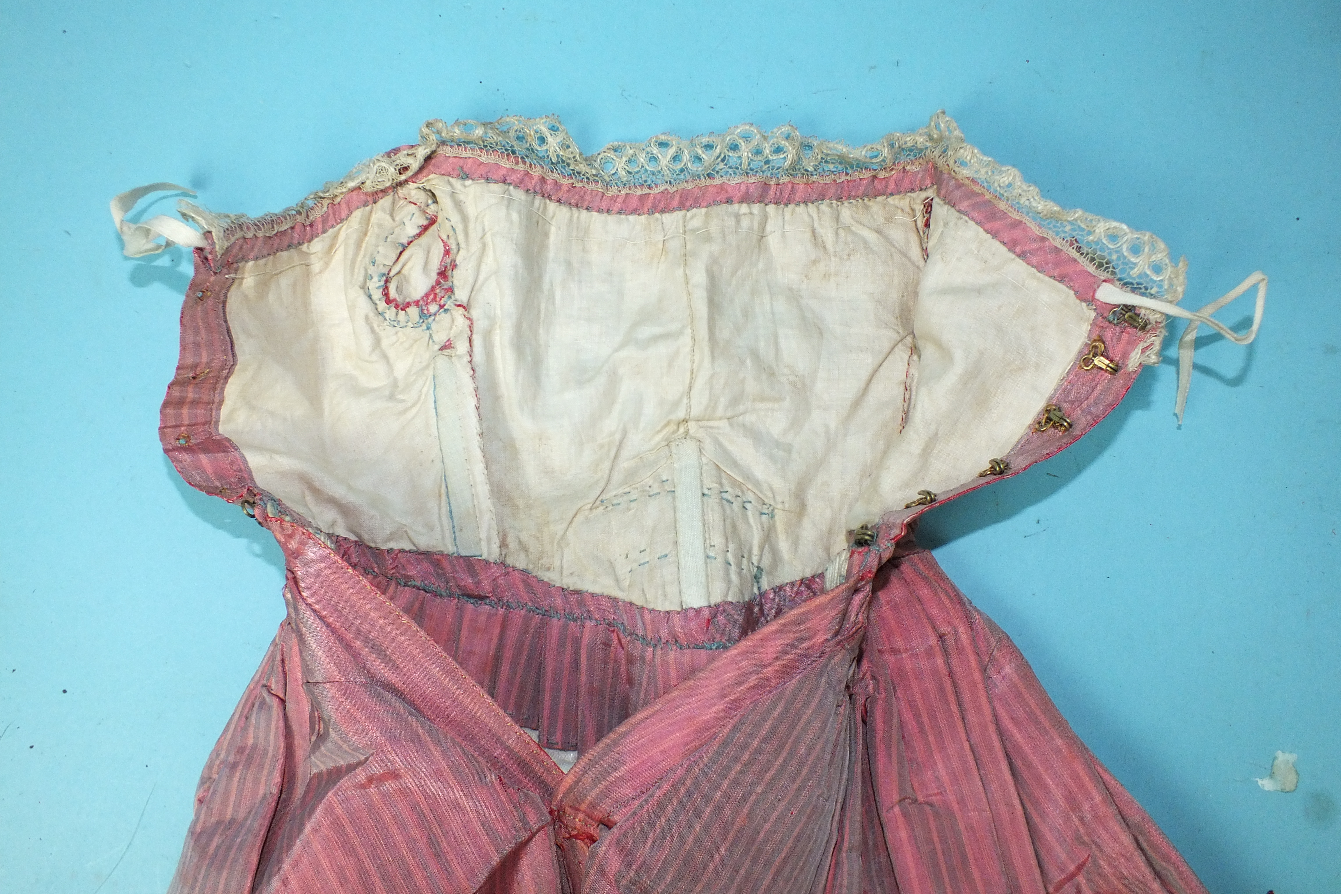 Lot 500 - A Victorian doll's silk dress c1840's, of pink striped silk with boned bodice, lace trimming and