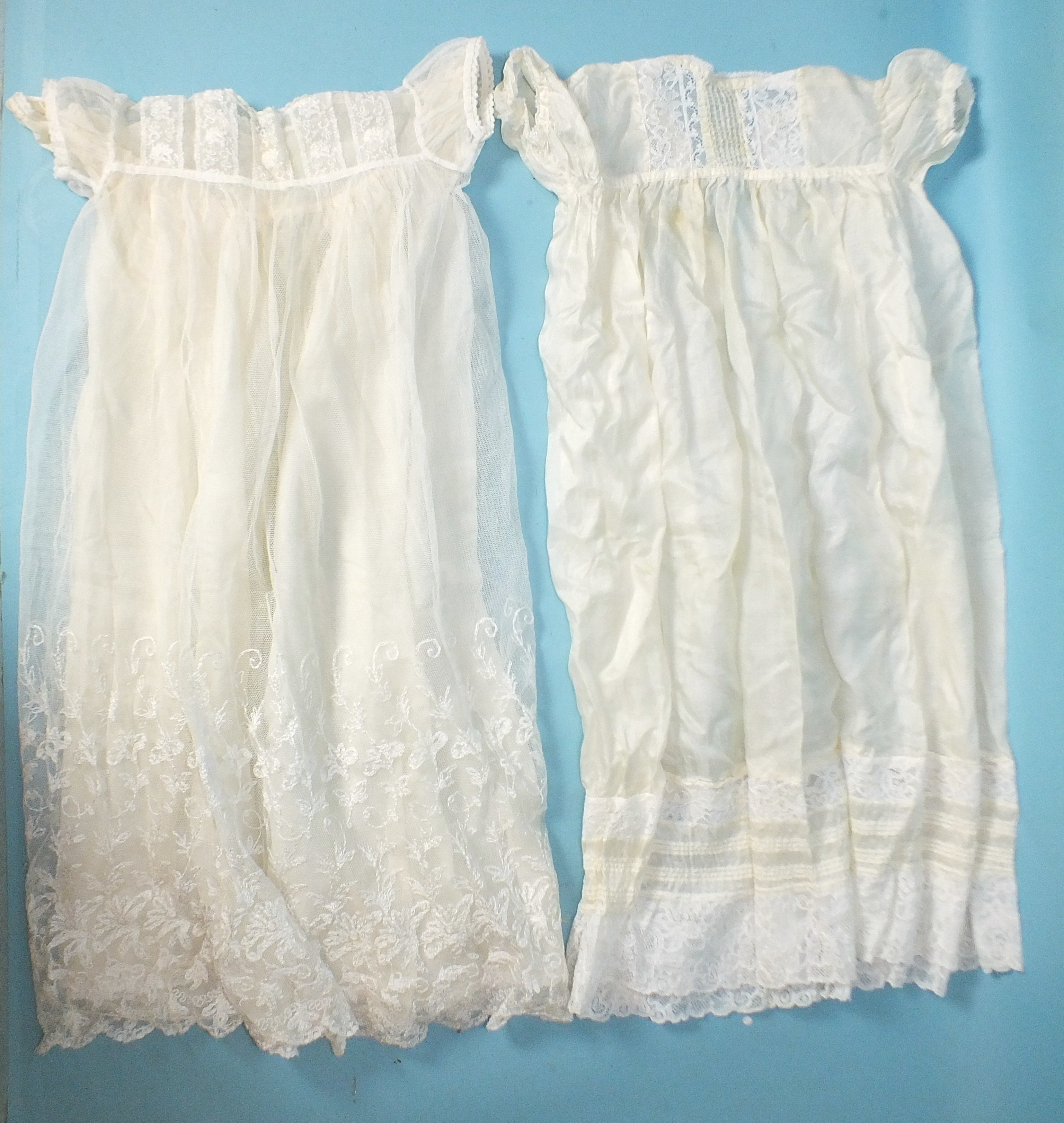 Lot 520 - An early-20th century baby dress of net, needle-run with flowers on the bodice and hem, over a