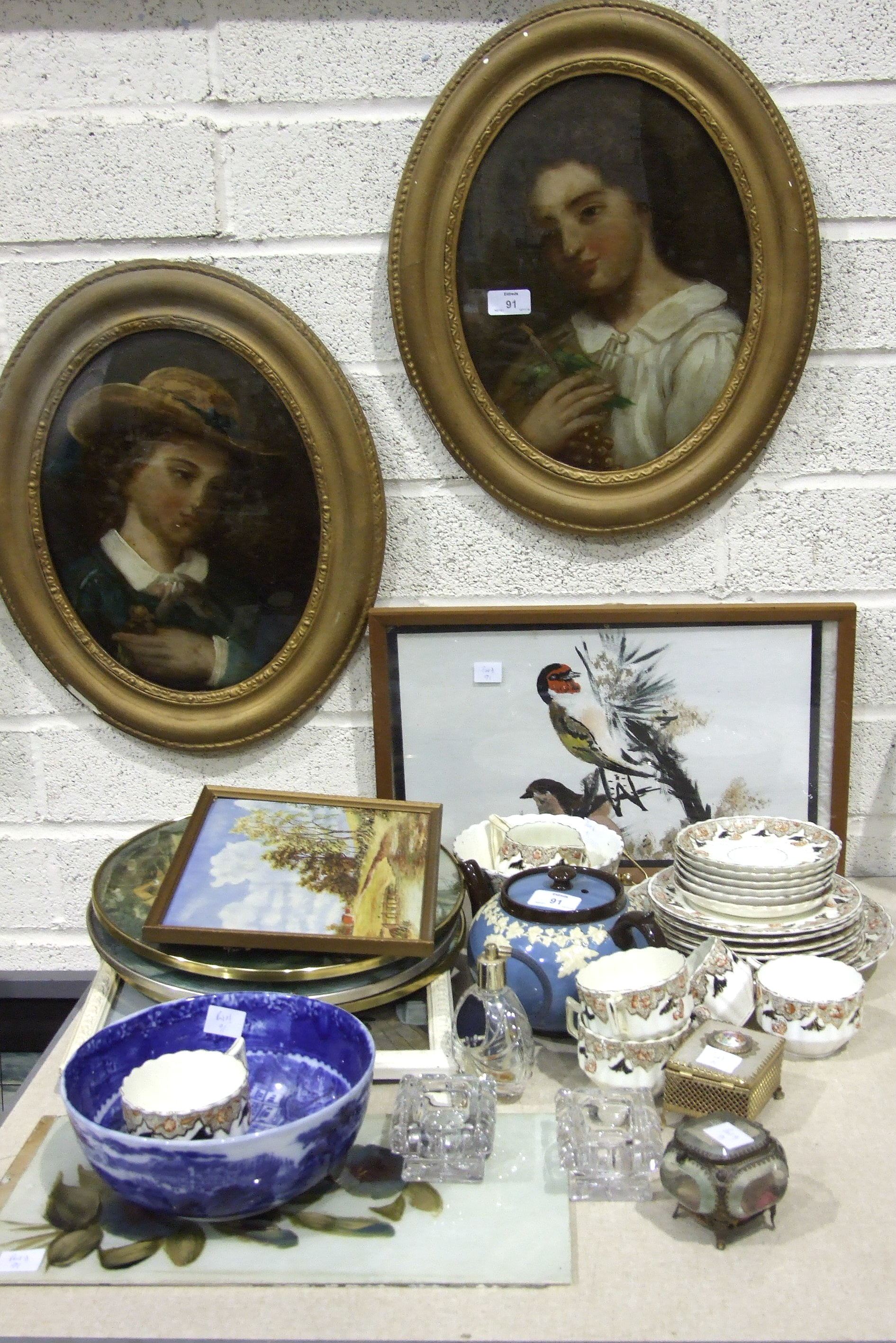 Lot 91 - A pair of 19th century oval paintings on glass, depicting a young woman holding a bunch of grapes, a