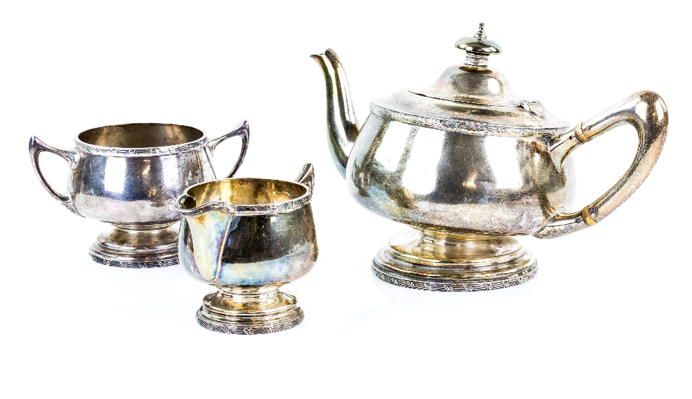 Lot 2019 - George V silver three piece tea service, comprising teapot, cream jug and sugar bowl, with floral