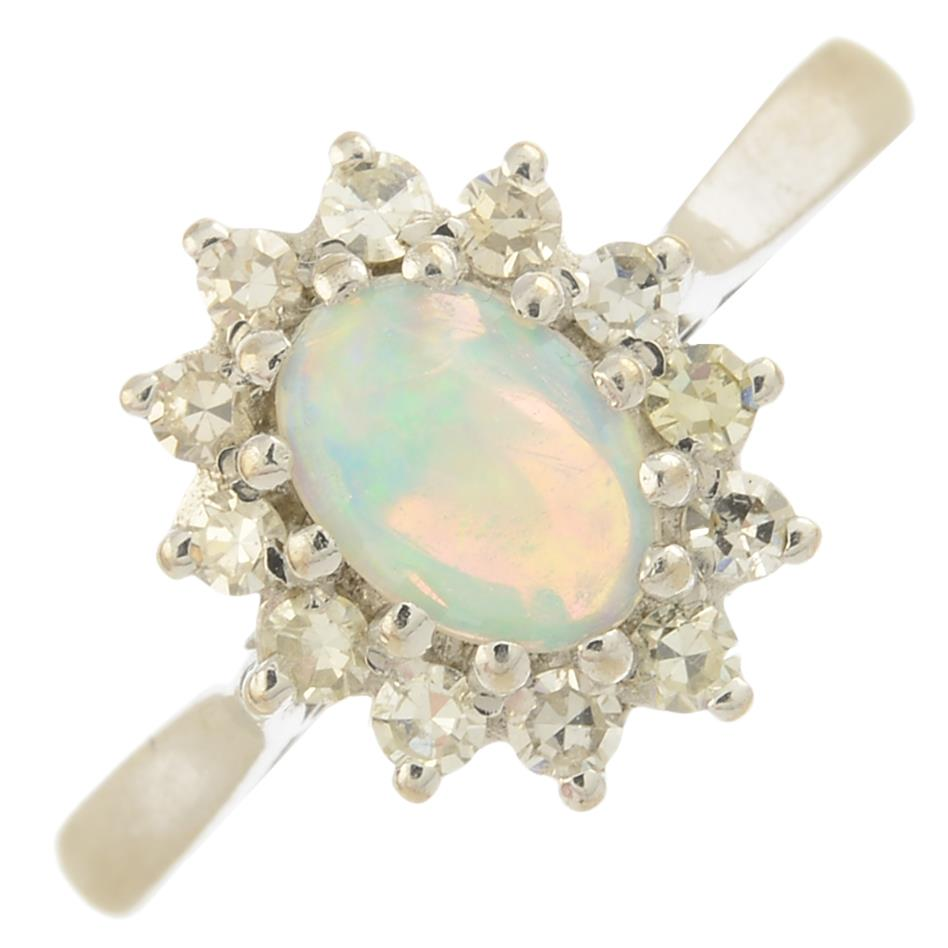 Lot 27 - An 18ct gold opal and diamond cluster ring.Approximate opal dimensions 7.1 by 5.8 by 2.4mms.