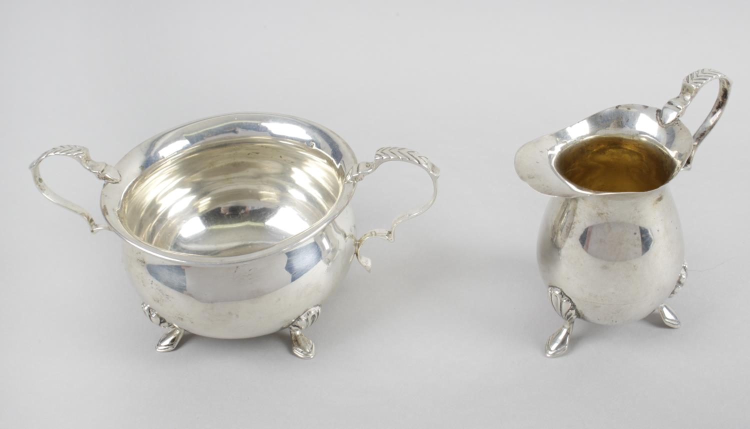 Lot 21 - An Edwardian silver twin-handled sugar bowl and matching cream jug,