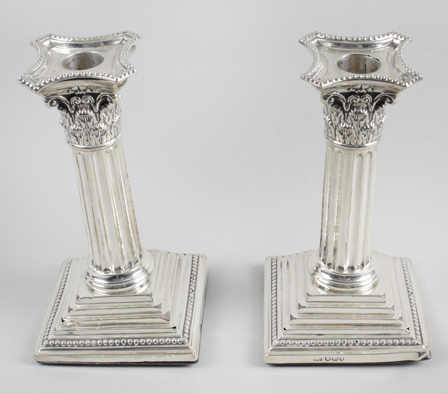 Lot 17 - A pair of late Victorian silver mounted candlesticks,