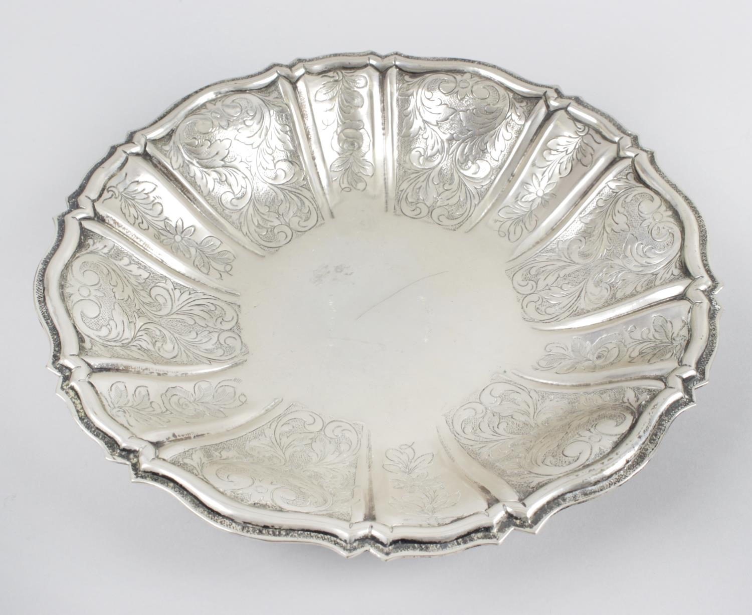 Lot 170 - A Scandinavian dish, the circular lobed form chased with floral scrolls to the raised edge.
