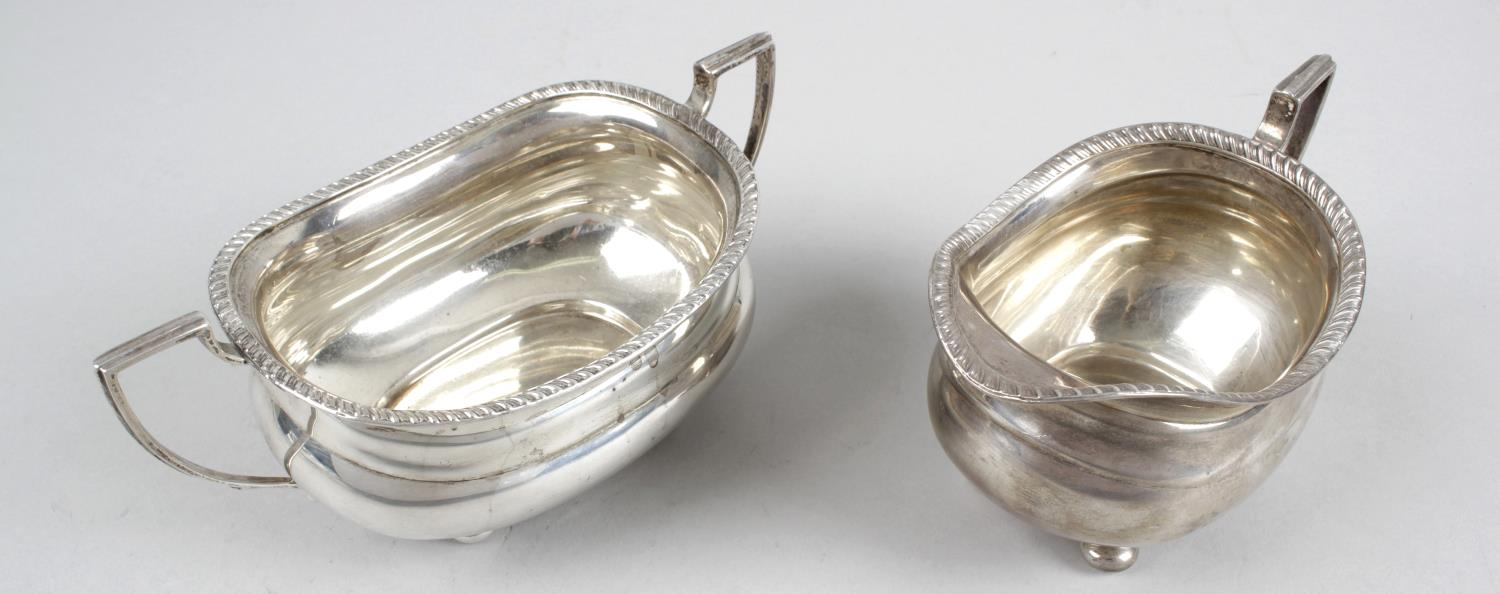 Lot 83 - A 1930's silver twin-handled sugar bowl and matching cream jug,