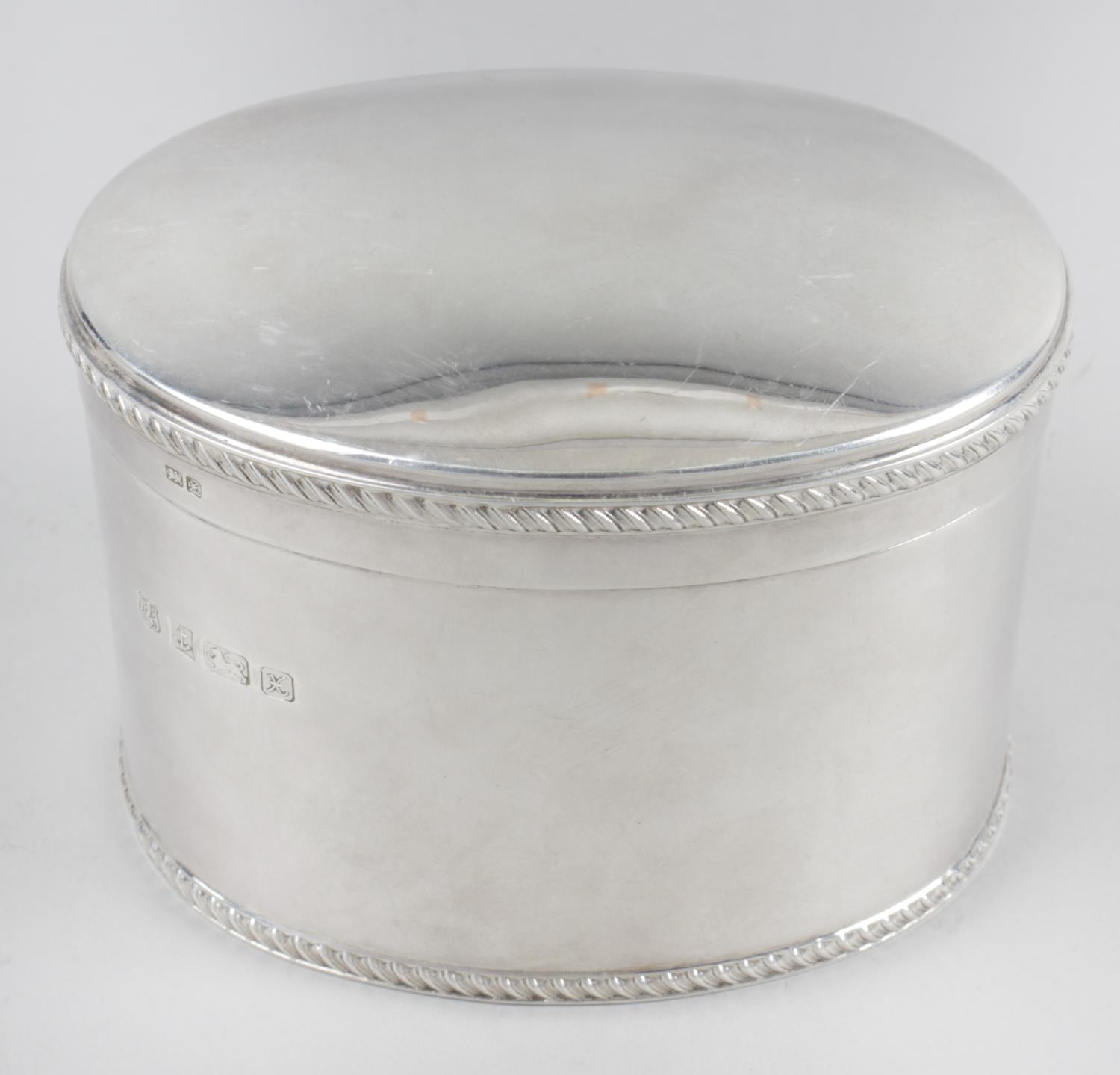 Lot 126 - A modern silver caddy, of plain oval form with oblique gadrooned rim to the hinged cover and base.