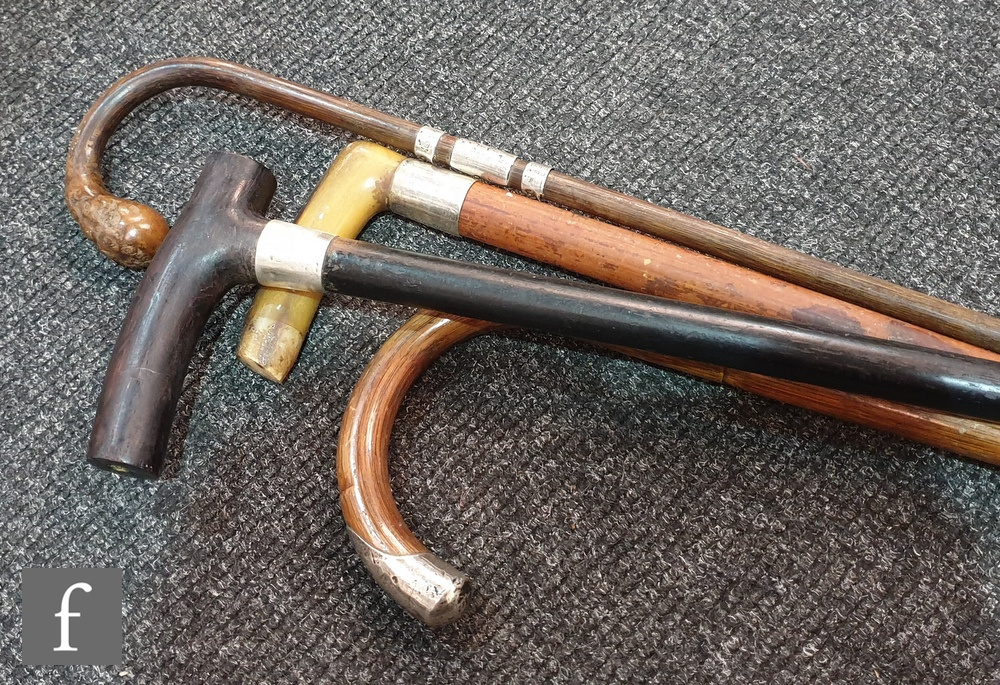 Lot 676 - Two silver banded walking sticks and a silver ended walking stick. (3)