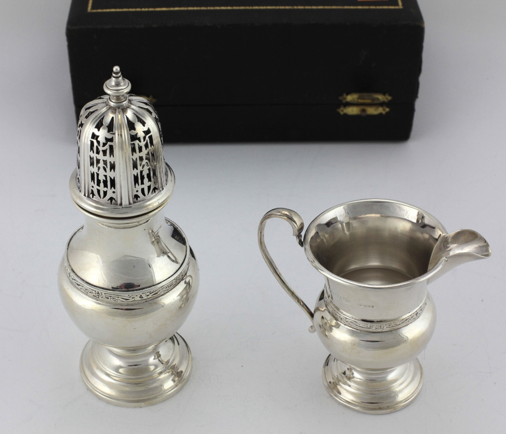 Lot 54 - A cased Presentation silver Sugar Castor and Cream Jug, decorated in the Celtic taste, by S.
