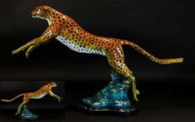 A Large Coldpainted Bronze In The form Of A Leaping Cheetah Raised on organic form black marble