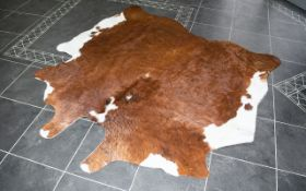 Large Cowhide Rug Of traditional form in chestnut and white hair, 6ft square,