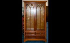 A Yew Wood Display Cabinet Comprising glazed doors above two short and one long drawer.