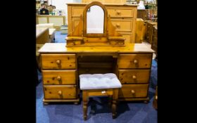 A Pine Dressing Table comprising two banks of three drawers complete with swivel mirror and stool.