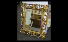 Bevelled Glass Mirror Large decorative mirror in ornate gilt swept reproduction rococo frame.