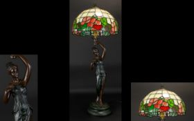 A Reproduction Tiffany Style Lamp Bronzed resin figural lamp with canopy shade in leaded opaque