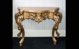 A Reproduction Rococo Style Console Table Pale gilt table with moulded curlicue form apron and legs.