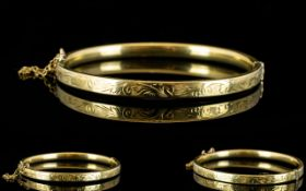 A 9ct Gold Hinged Bangle with Safety Chain, Stylised Floral Decoration to Outer Side of Bangle. c.