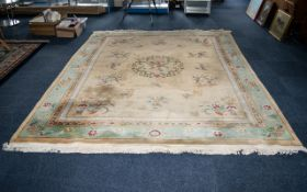 A Large Oriental Wool Rug Cream ground with triple border detail in foliate and Greek key Intarsia.