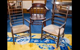 A Pair Of Lancashire Ladder back Chairs comprising armchair and rocker with traditional rush seats.