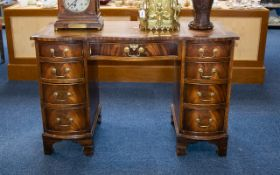 A Serpentine Fronted Pedestal Desk Comprising central drawer between two banks of four graduating