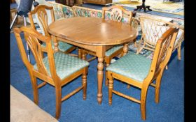 A Beechwood Dining Table And Chairs extending table of oval form with x4 accompanying fiddle back,