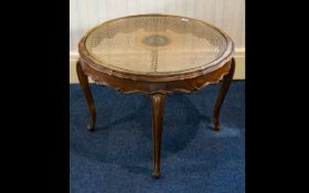 A Circular Occasional Table raised on scroll feet with fluted edge and glass inlay top with woven