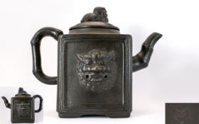 Oriental Yixing Teapot Of Square form with lion masks to body and bamboo form handle and spout.