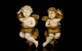 A Pair Of Reconstituted Putti Wall Sconces Each in the form of winged putti with gilt painted