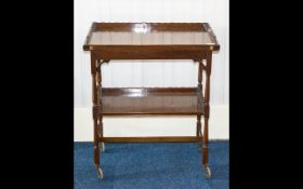 A 1920's Mahogany Trolley Of rectangular form with tilt and swivel top revealing a brown baize card