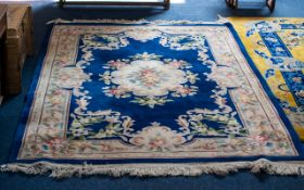 Oriental Style Wool Rug - of traditional floral design on taupe ground with wide cobalt blue border