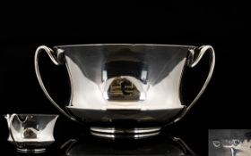A Silver Arts And Crafts Twin Handle Bowl Of small proportion with flared rim and stylised leaf and